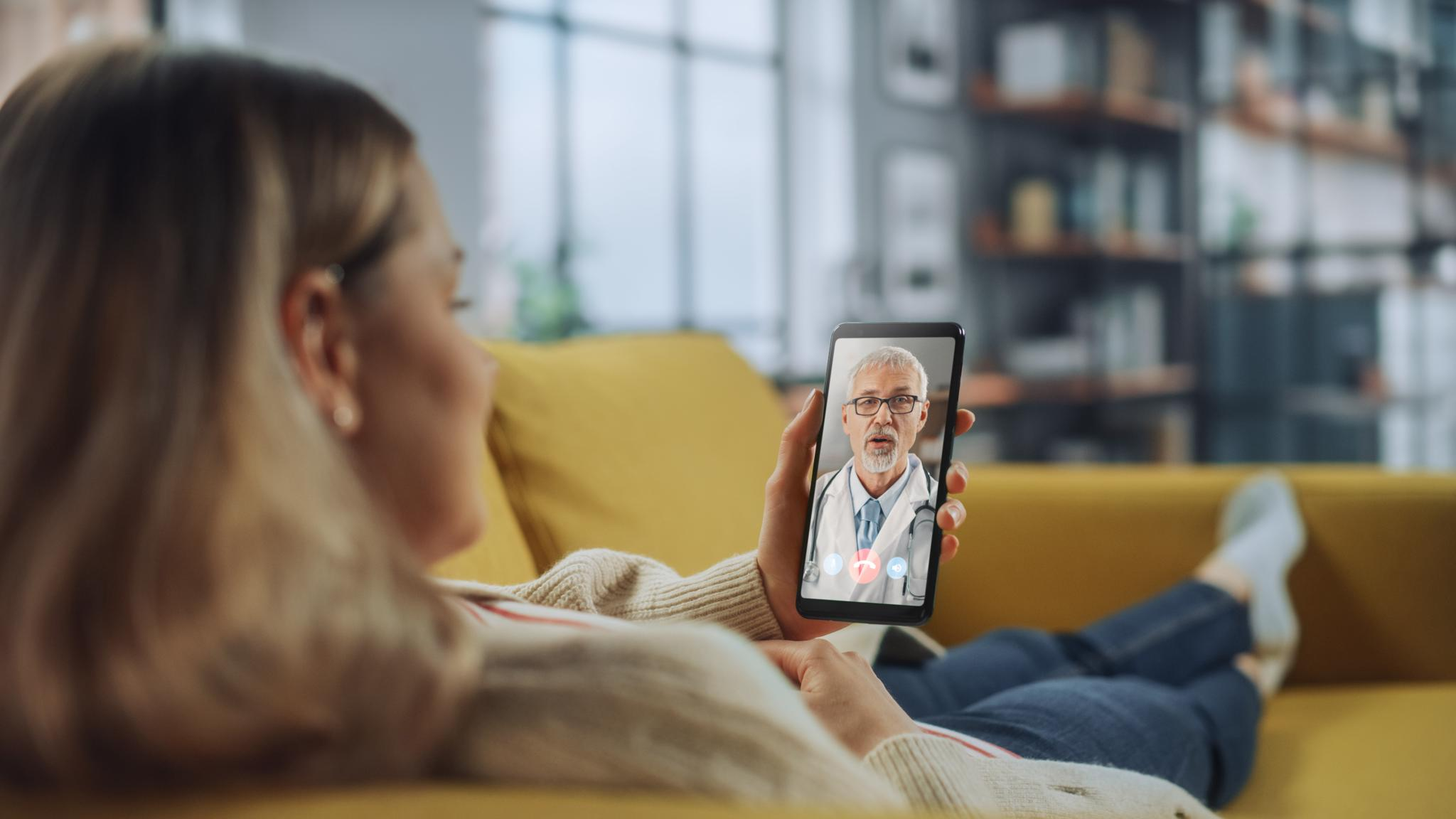 Close Up of a Female Chatting in a Video Call with Her Senior Family Doctor on Smartphone from Living Room. Ill-Feeling Woman Making a Call from Home with Physician Over the Internet.