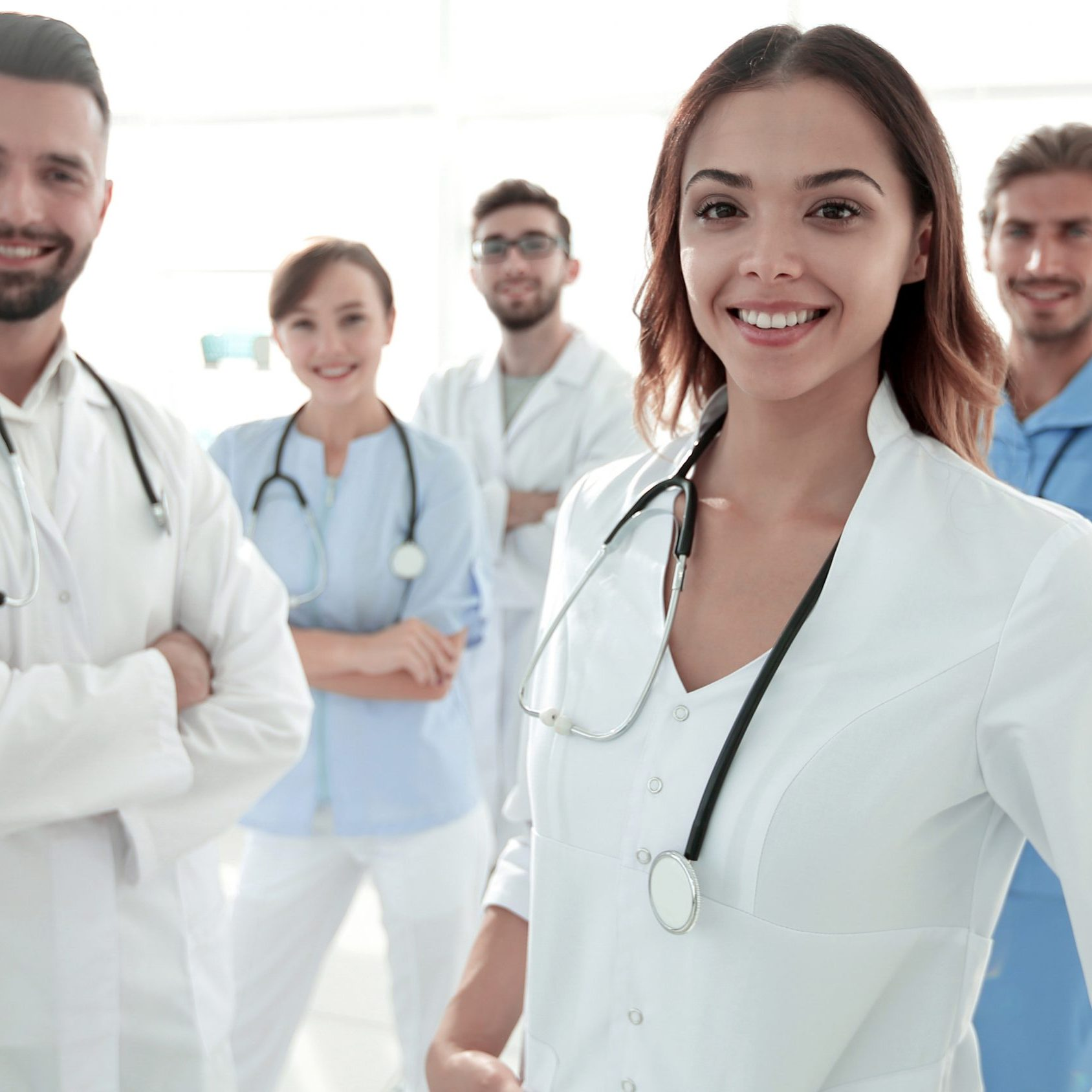 Attractive female doctor with medical stethoscope in front of medical group.photo with copy space